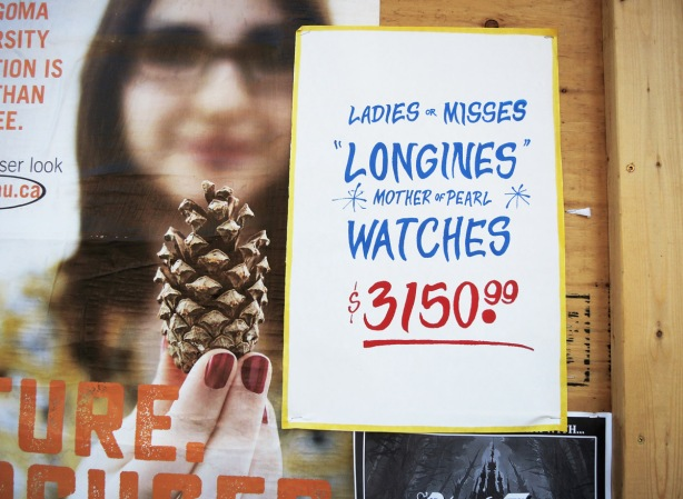 advertising posters and graffiti on a wall, graffiti is a mock ad for ladies watch at $3150. ad is woman holding a pine cone
