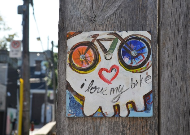 a little painting of a bike and a heart that makes it look like the wheels are eyes and the heart is a mouth