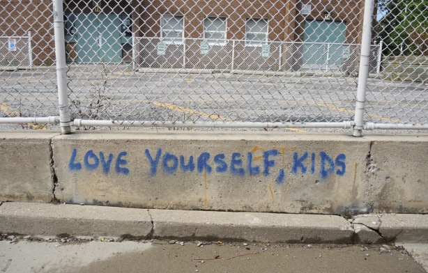 blue spray paint graffiti words on concrete by a chainlink fence surrounding a school playground and parking lot that say Love Yourself Kids
