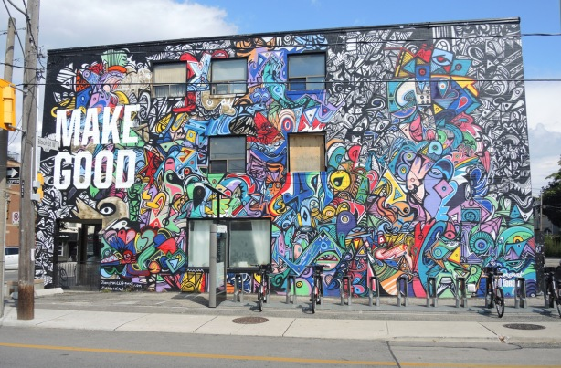 large colourful mural by J. Chiale on the side of a building. Large white letters that say Make Good.