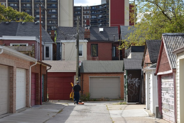 a man walks a lawn mower down a short alley, garage doors on both sides of him as well as in front of him, back of houses behind the garages and taller apartment buildings behind that.