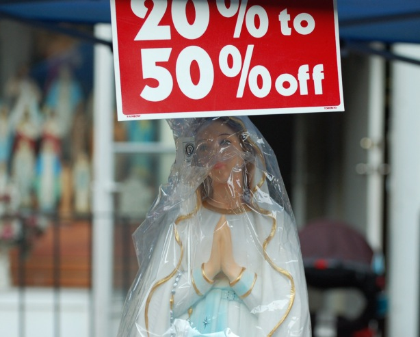 a statue of the VIrgin Mary wrapped in plastic, for sale at an outdoor sale, with a sign above her head that says 20% to 50 % off.