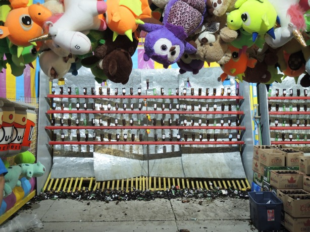 rows of empty beer bottles as targets at a midway game of throwing balls at bottles, broken glass below, stuffed animal prizes hanging above