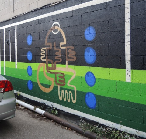 partially finished mural on black background in an alley, green stripes near the bottom, blue circles beside brown squiggles, milk x weed