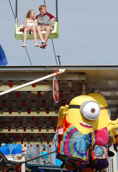 two people ride on the Skyride above the midway at the ex, a large minion, stuffed toy prize, hangs below them