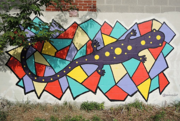 a dark purple salamander in a street art painting on a background of orange, yellow, and light blue polygonal shapes with 3 to 5 straight sides on a wall with a tree to the left