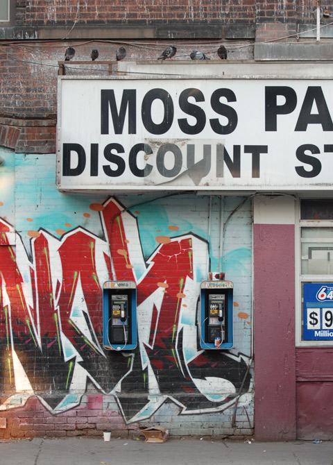 two Bell telephone booths, small version, mounted on a wall with street art painted on it, beside the window of a convenience store with a 649 ad in the window. Sign over the window says Moss Park Discount Store