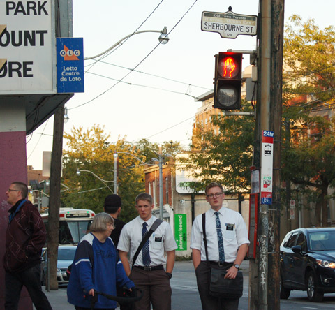people standing on a corner waiting to cross the street, including a woman dressed in blue who is using a walker, plus two Morman men in their white shirts and black ties.