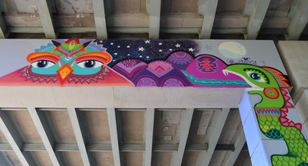 an owl with the night sky and stars, purplish mountains, part of a colourful mural on concrete pillars under the Gardiner Expressway , a green snake with a long tongue on the vertical pillar on the right