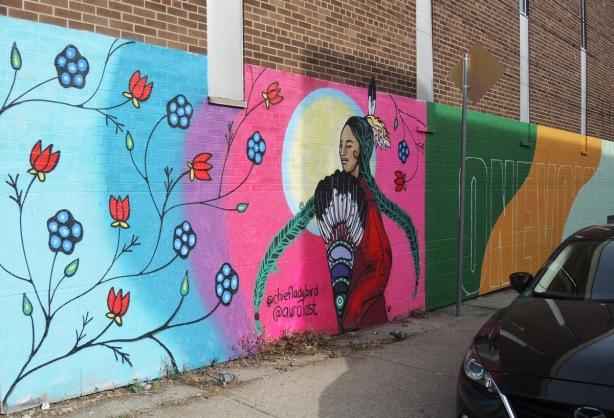 part of a mural by chief ladybird and aura of an indigenous woman with a feather in her hair, in front of the sun and circles of colour, red and blue flowers on the outer layer of colour (light blue)