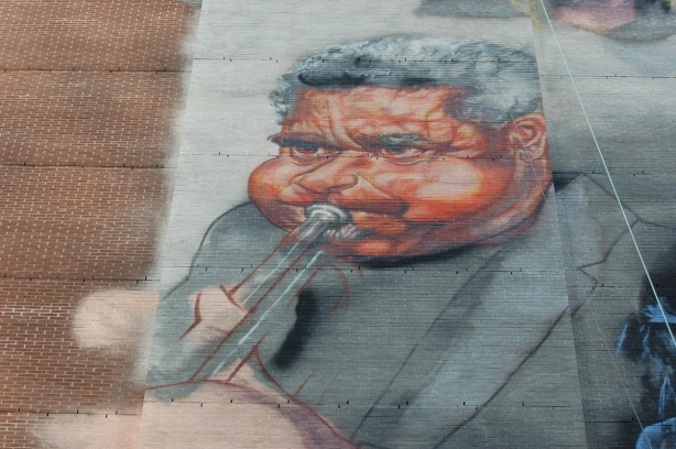 part of a music mural, a trumpet player, male, with graying hair,