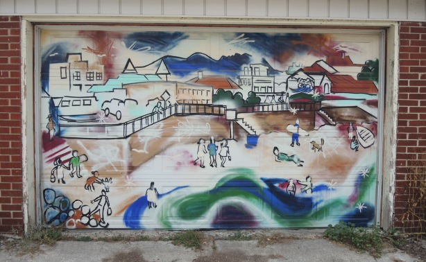 seaside town mural, buildings, water, beach, people, seawall, on a garage door in an alley, laneway