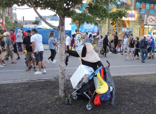 muslim woman in burka stands by a small tree with a stroller laiden down with parcels and bags, other people at the Ex are in the background