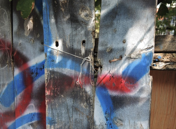 red, white, and blue spray paint on three wood slats of a fence, tied together with string, some nails sticking out