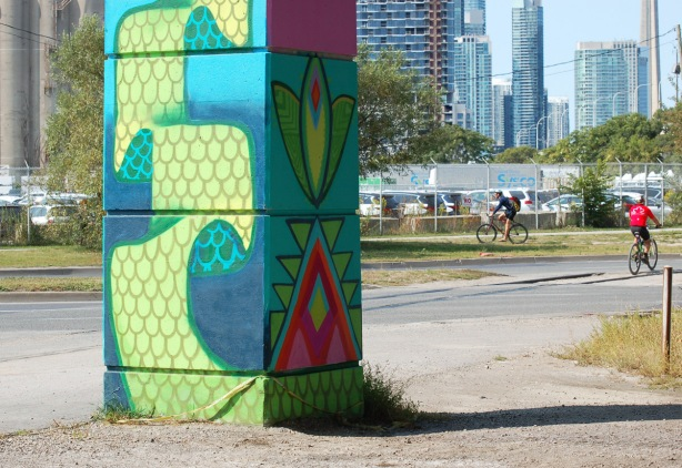 part of a colourful mural on concrete pillars under the Gardiner Expressway, cyclists in the distance, pillar with street art in the foreground