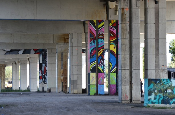 painted pillars under an elevated expressway, murals