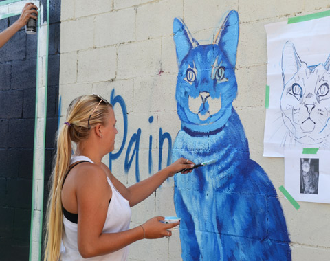 a woman with long blond hair, Stacey Kinder, is painting a picture of a blue cat on a wall,