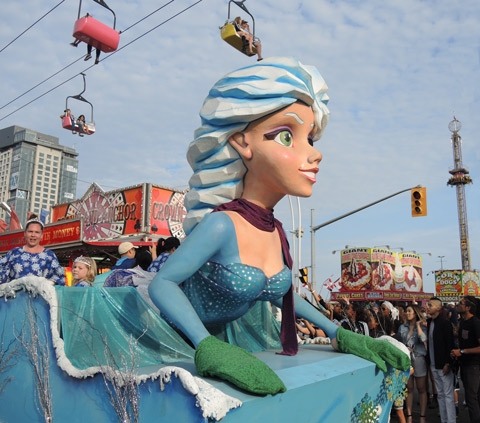 a float in a parade shaped like Elsa from the movie Frozen, passes through the exhibition grounds.