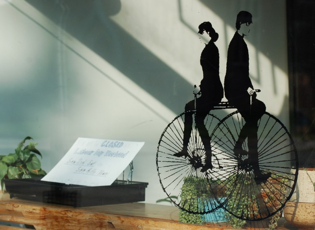 a picture of two people riding old fashioned bicycles, in black, in a window.