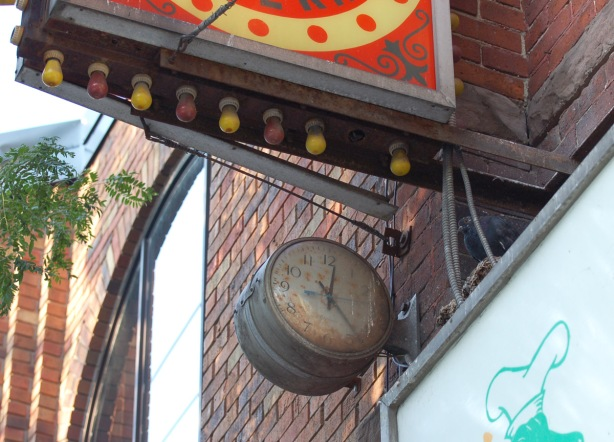 a small round clock, old, attached to an outside wall, underneath a bright sign with red and yellow light bulbs around it.