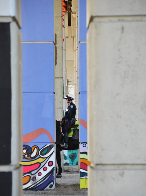 policeman on horseback as seen through two pillars under the Gardiner expressway
