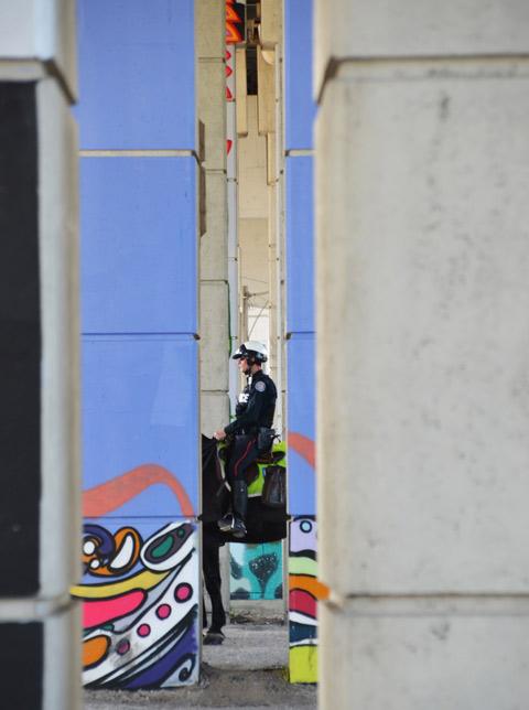 policeman on horseback as seen through two pillars under the Gardiner expressway
