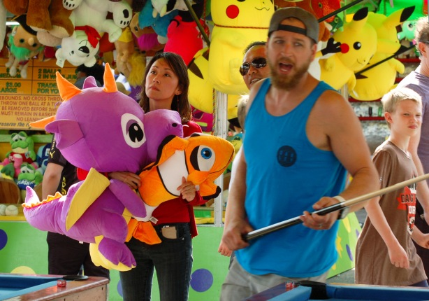 a man with a pool cue playing a game at the CNE midway, with a woman with an armful of large stuffed prizes behind him