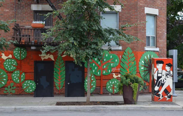lower part of a brick building has been covered with a mural that is orange background, and cut out (wood) flat green trees in various shapes. A real tree grows in front of it, a metal traffic box is painted with a scene of two people walking with the same orange background