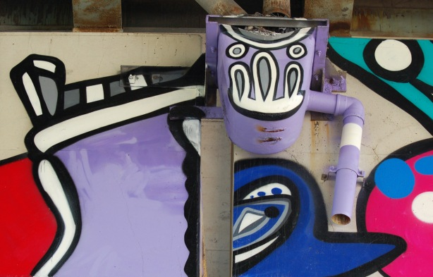 part of a colourful mural on concrete pillars under the Gardiner Expressway - drain under the Expressway has been painted light purple and made into a head. Drainpipes are the arms