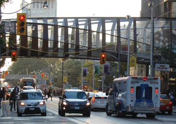 glass pedestrian bridge over a street, Queen Street, with traffic and people as well as an ambulance, late afternoon