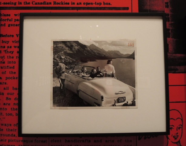 photo in an exhibit of a group of tourists in a convertible car with California plates parked beside the road and overlooking a mountain lake. An RCMP officer stands beside the car.