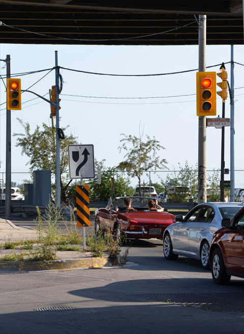 cars stopped at a red light at the south end of Cherry street where it intersects with the Lakeshore, under the Gardiner, a red convertible is the first car at the light.