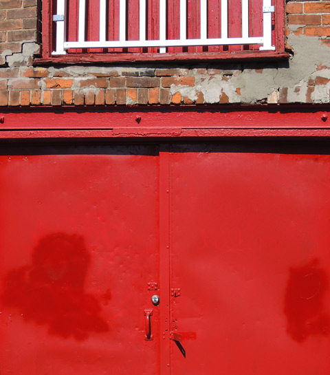 part of a bright red double metal door in a brick building
