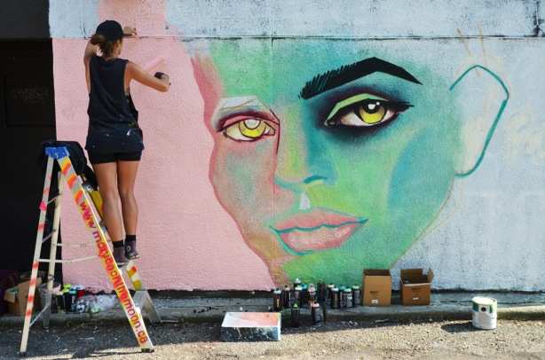 woman rolling paint to make pink background on a mural