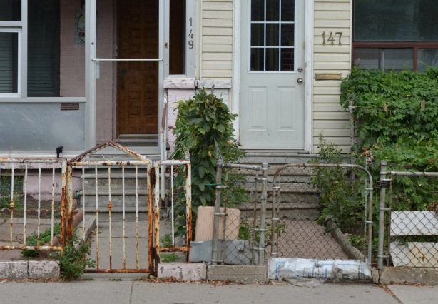 a fence across the front of two houses, each with their own sidewalk and gate.