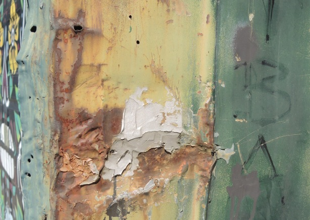 a grey plaster attempt to patch a broken rusted metal panel on the side of a garage - rust in shades of yellow and brown, a painted green stripe
