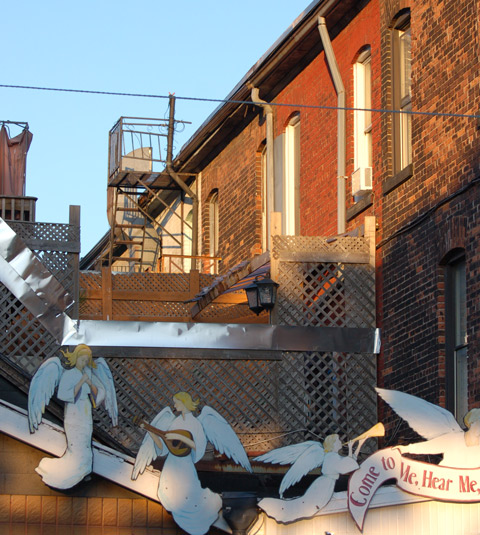 wooden angel cutouts decorate the roofline of a small building
