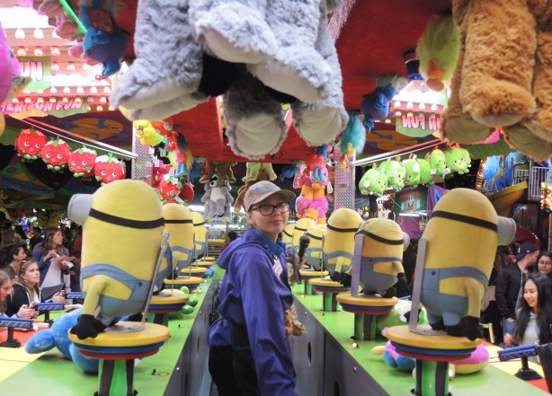 woman running a game at the CNE, she is surrounded by prizes such as stuffed minions and other animals