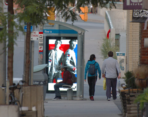 a lit advertisement in a bus shelter of two men in Roots clothes, a young man sits on the bench in the bus shelter while two people walk past it on the sidewalk
