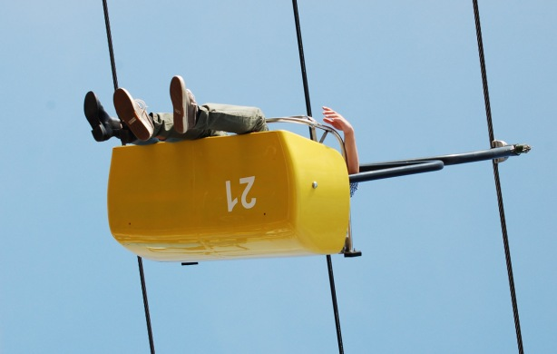 from below, two people riding on the Skyride, an arm hangs over the side, and there appear to be only three feet