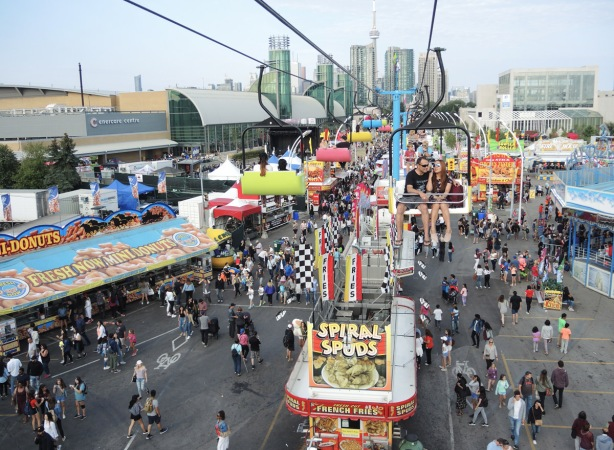 on the Skyride at the Ex, overlooking the CNE below, people walking around, booths selling food such as mini donuts and spiral spuds