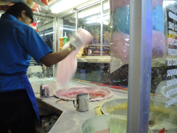 a man collected cotton candy that is spinning in vats in front of him