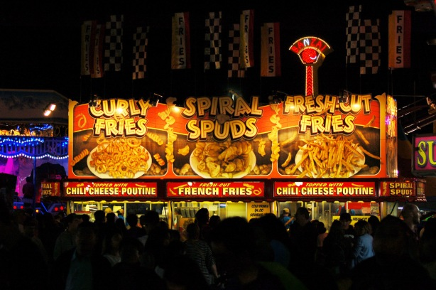 evening photo, darkness, bright lights of the signs for curly fries, spiral spuds and fresh cut fries, food for sale at the ex