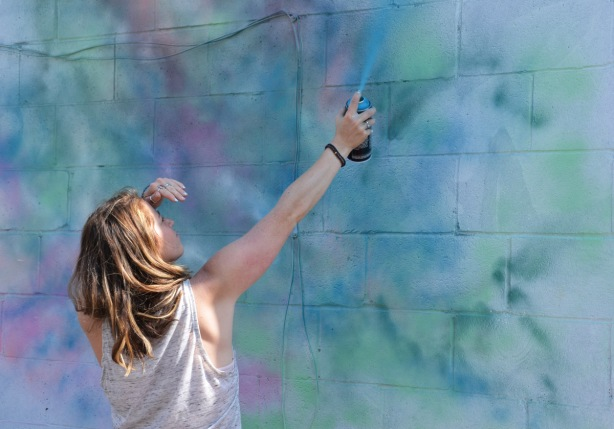 a woman sprays paint, light blue, onto the background of a mural that she's painting, blue, green and pinks that merge together with no defined lines or edges