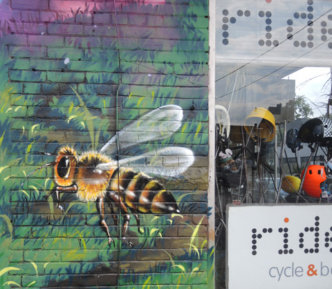 part of a larger mural by Clandestinos (Shalak Attack and Bruno Smoky) on the side of Riders bike store, a large bumble bee by the front window