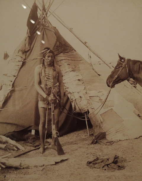 vintage photo of a native American man in traditional clothes holding a rifle and a horse and a lead. Standing outside a teepee