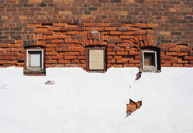 three small windows in a wall, the top part of the wall is brick and the bottom is plaster that has been painted white