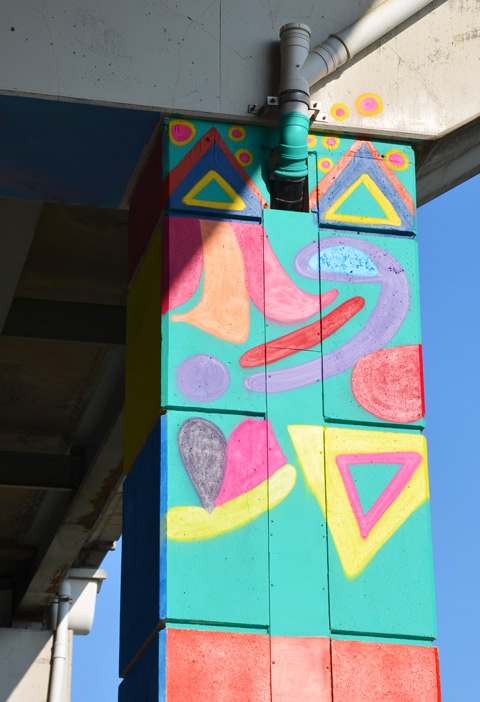 part of a colourful mural on concrete pillars under the Gardiner Expressway - abstract in turquoise and other bright colours, triangles and lines and blobs