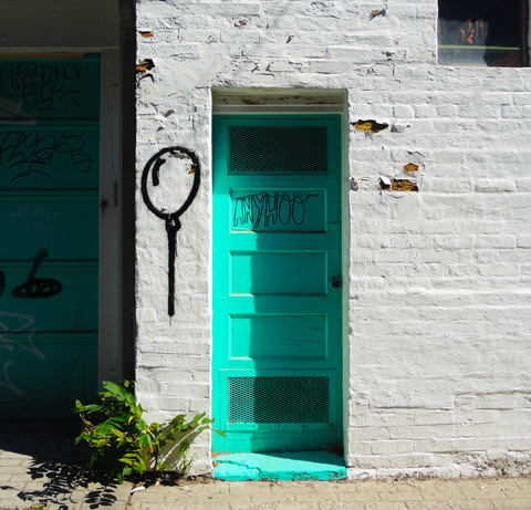 a bright turquoise door in a building that has been painted white - some of the old brick shows throw the peeling paint.