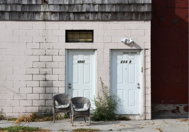 two grey wicker chairs in front of two adjacent white doors on a concrete wall. the building beside is orange
